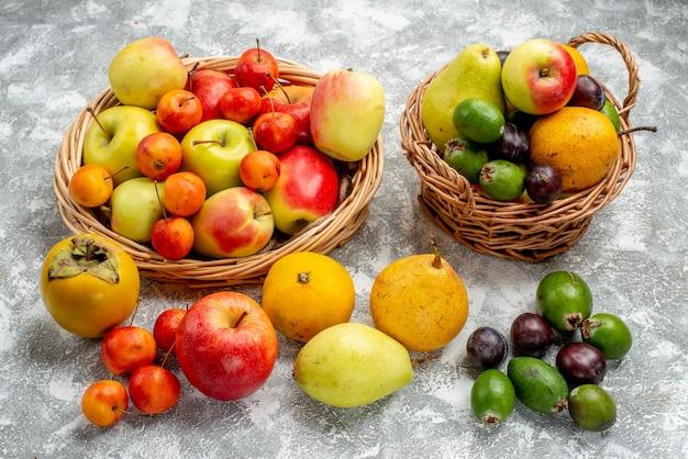Vista inferior manzanas y ciruelas rojas y amarillas feykhoas peras y caquis en las cestas de mimbre y también en el suelo