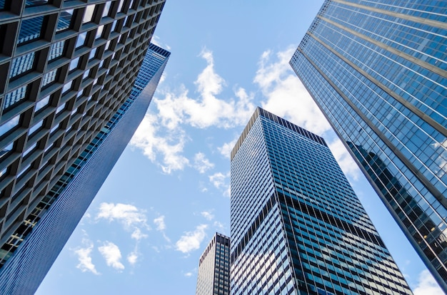 Vista inferior de modernos rascacielos en el distrito de negocios de manhattan, nueva york, estados unidos. concepto de negocios, finanzas, bienes raíces
