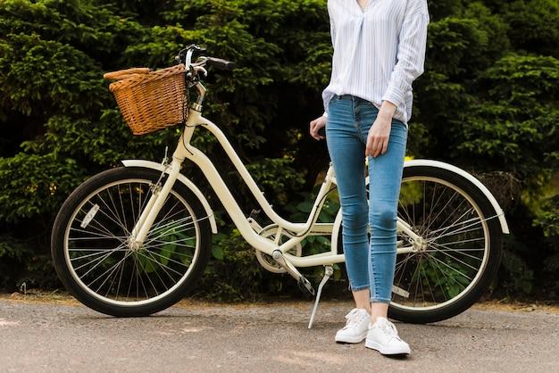 Vista inferior mujer posando al lado de bicicleta
