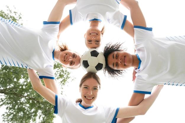 Vista inferior mujeres felices sosteniendo bola