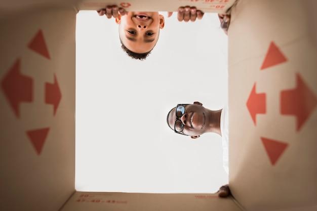 Vista inferior padre e hijo mirando dentro de una caja