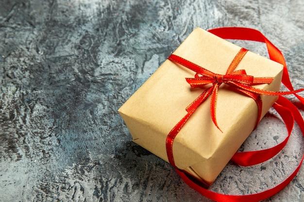 Vista inferior pequeño regalo atado con cinta roja en la oscuridad