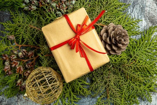 Vista inferior pequeño regalo atado con cinta roja en ramas de pino bolas de navidad de piñas