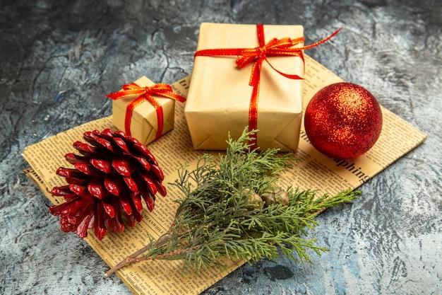 Vista inferior pequeños regalos atados con cinta roja rama de pino bola roja en periódico sobre fondo oscuro