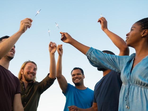 Vista inferior de personas felices de pie con luces de bengala. sonrientes amigos pasar tiempo juntos al aire libre. concepto de celebración
