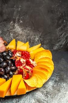 Vista inferior de piezas de queso, uvas y granada en una placa ovalada para servir sobre fondo oscuro