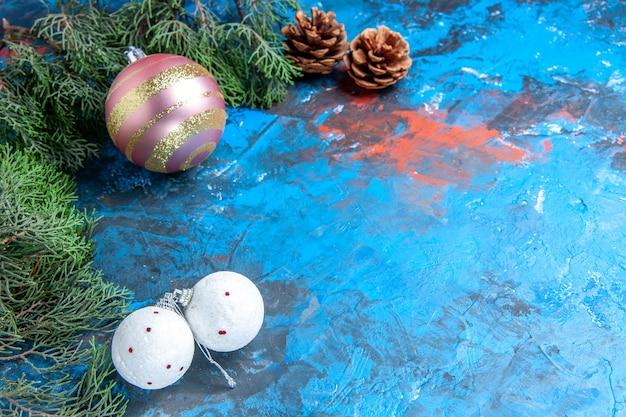 Vista inferior de ramas de pino piñas bolas de árbol de navidad sobre fondo azul-rojo con espacio de copia