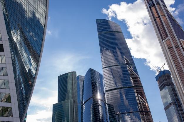 Vista inferior de los rascacielos de la ciudad de moscú con diseño futurista con reflejo de nubes