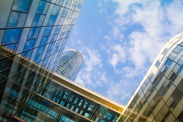 Vista inferior de los rascacielos de cristal del distrito de negocios de parís la defense contra un cielo azul nublado