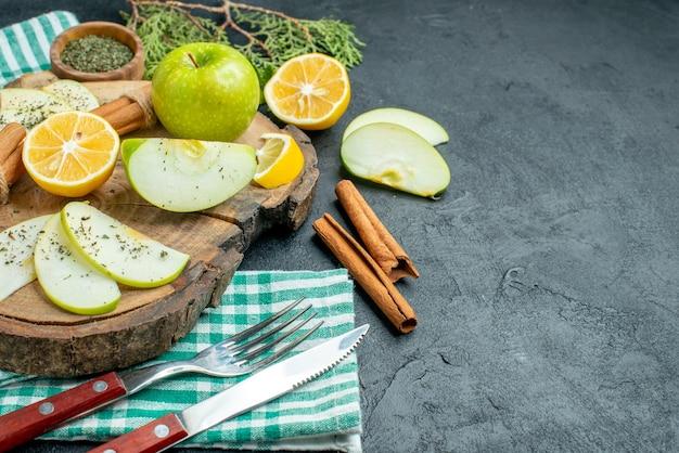 Vista inferior rebanadas de manzana palitos de canela y rodajas de limón manzana sobre tablero de madera ramas de pino un tenedor y cuchillo sobre una servilleta verde sobre una mesa negra con espacio libre