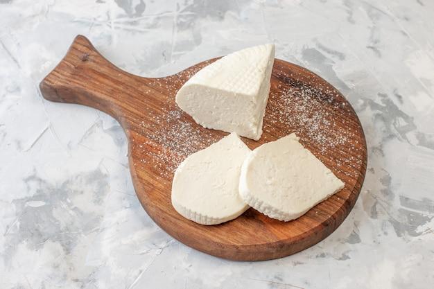 Vista inferior rebanadas de queso blanco sobre tablero de madera en la mesa