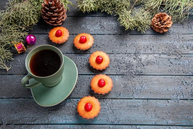 Vista inferior redondeada cereza cupcakes ramas de abeto juguetes de navidad conos y una taza de té sobre fondo de madera oscura.