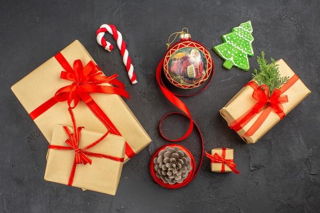 Vista inferior de los regalos de navidad en la cinta de papel marrón, el árbol de navidad de juguete en el periódico en la oscuridad.