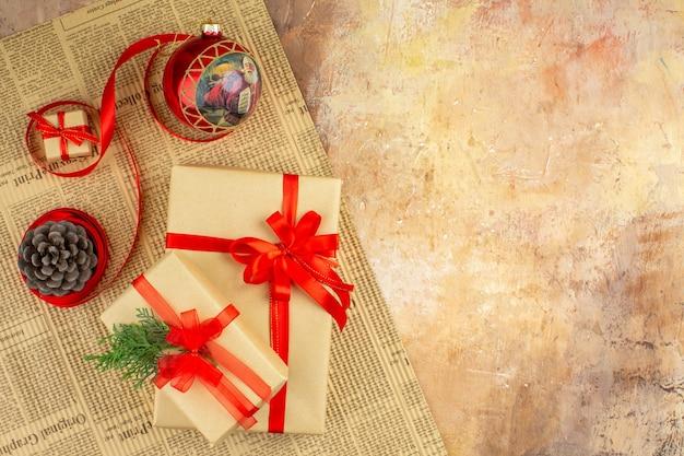Vista inferior de regalos de navidad en cinta de papel marrón juguete de árbol de navidad en periódico sobre fondo oscuro