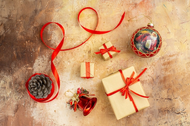 Vista inferior de los regalos de navidad en la cinta de papel marrón juguetes del árbol de navidad en el periódico sobre fondo beige