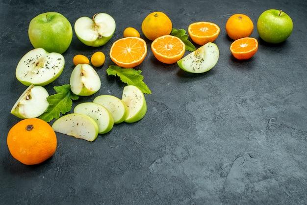 Vista inferior de las rodajas de mandarina de manzana deja cumcuat en el espacio libre de la mesa oscura