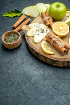 Vista inferior de rodajas de manzana manzana palitos de canela rodajas de limón sobre tablero de madera con polvo de menta seca en el lugar de copia de tierra negra