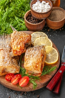 Vista inferior sabroso pescado freír rodajas de limón cortar tomates cherry en una tabla de cortar diferentes especias en tazones sobre fondo negro
