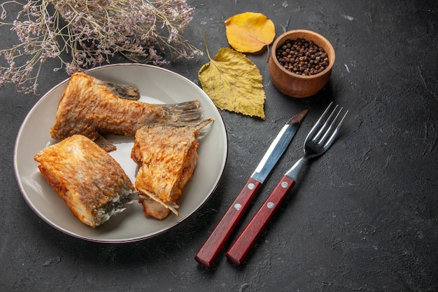 Vista inferior sabroso pescado frito en plato tenedor y cuchillo rama de flor seca pimienta negra en tazón de madera sobre mesa negra