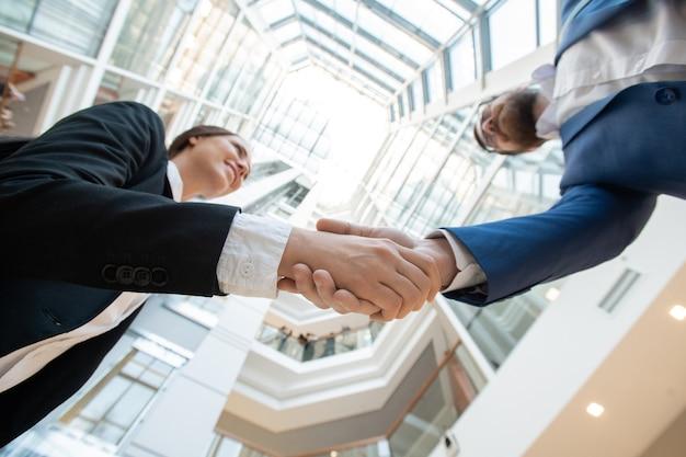 Vista inferior de socios comerciales exitosos en trajes haciendo apretón de manos contra el panorama del centro de la oficina