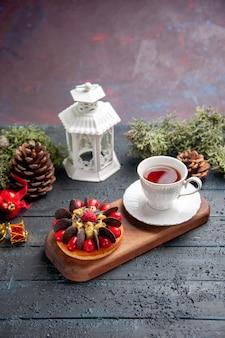 Vista inferior de una taza de té y pastel de bayas en un plato de madera con piñas, juguetes navideños y linterna blanca en la mesa de madera oscura.