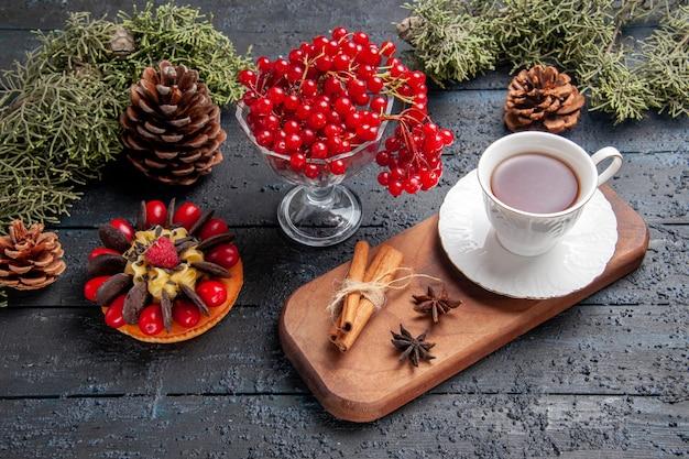 Vista inferior de una taza de té de semillas de anís y canela en un plato de madera para servir grosellas rojas en un pastel de baya de piñas de vidrio sobre suelo de madera oscura
