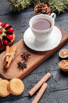 Vista inferior de una taza de té de semillas de anís y canela en un plato de madera para servir pastel de piña, naranjas secas y diferentes galletas sobre fondo de madera oscura.