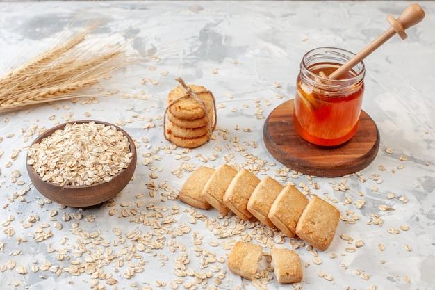 Vista inferior del tazón de madera con espigas de trigo avena esparcidos galletas de avena palo de miel en tarro de miel en la mesa
