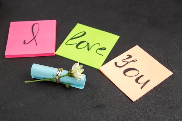 Vista inferior te amo escrito en notas adhesivas anillo de compromiso flor enrollada nota adhesiva sobre fondo oscuro