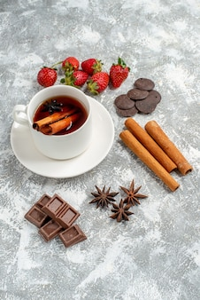 Vista inferior del té de semillas de anís y canela y algunas fresas, chocolates, semillas de anís y canela sobre la mesa