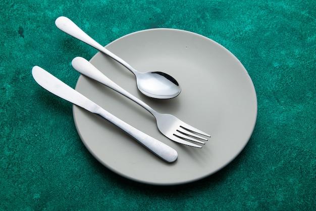 Vista inferior tenedor cuchara cuchillo en placa sobre superficie verde