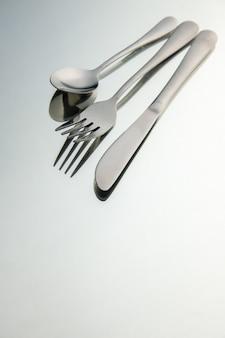 Vista inferior tenedor cuchillo cuchara en espejo con lugar de copia