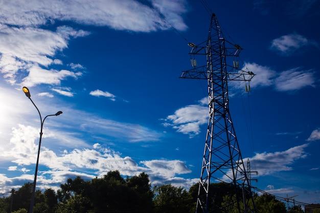 Vista inferior de la torre de redes eléctricas sobre fondo de cielo azul, alta tensión, concepto de electricidad