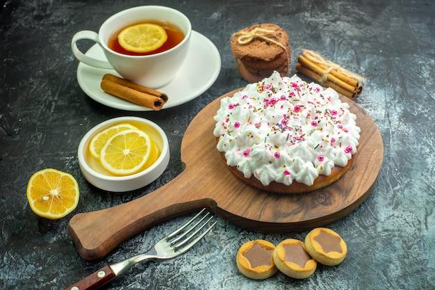 Vista inferior de la torta con crema pastelera en la tabla de cortar galletas tenedor palitos de canela taza de té con sabor a limón y canela en la mesa gris
