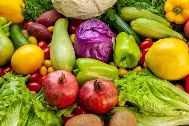 Vista inferior verduras y frutas calabacín pimientos membrillo tomates cherry col cumcuat limón granadas lechuga kiwi