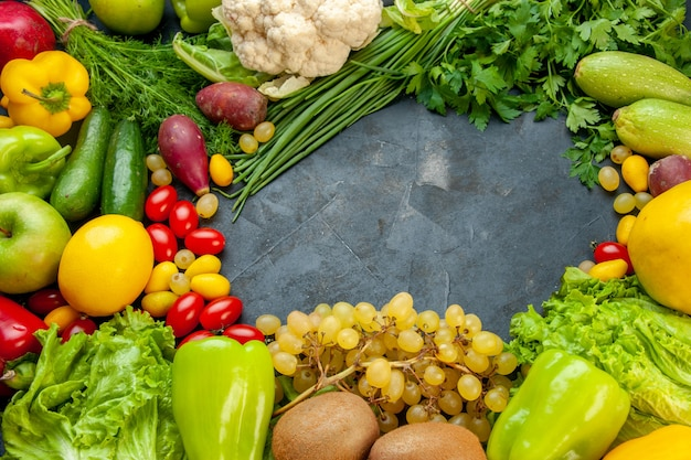 Vista inferior verduras y frutas lechuga cumcuat calabacín pimientos kiwi uvas perejil cebolla verde coliflor tomates cherry limón espacio libre