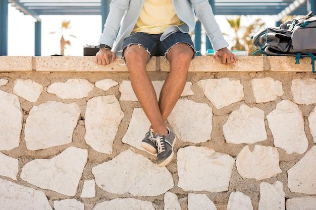 Vista inferior viajero sentado en una valla de piedra