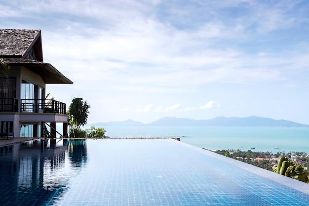 Vista infinita de la piscina en la montaña con nubes y cielo azul