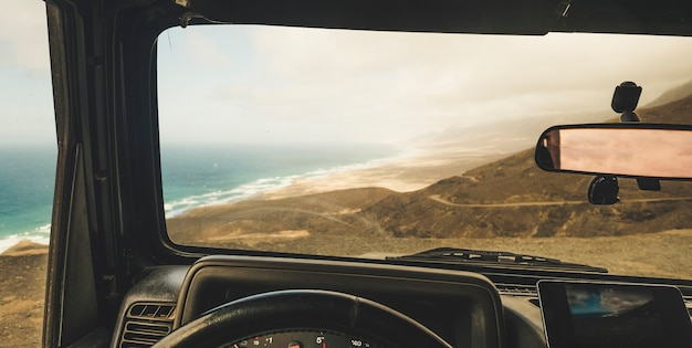 Vista interior del automóvil con sistema gps de teléfono móvil moderno para encontrar la carretera y usar mapas en un lugar escénico fuera de la carretera con vista a la playa y las montañas