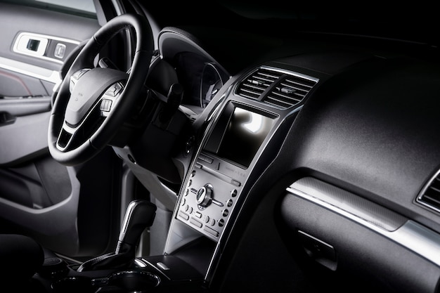 Vista del interior de un automóvil suv, tablero de instrumentos moderno con pantalla táctil, asientos de cuero negro ideales para el conductor