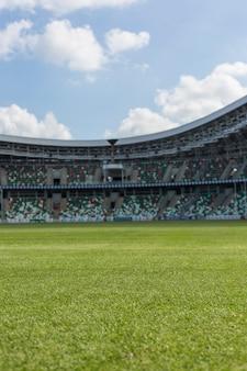 Vista interior del campo de hierba verde y asientos vacíos bajo el cielo azul nublado