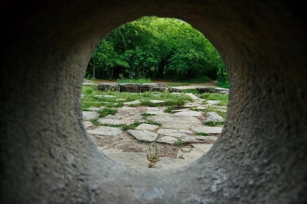 Vista interior de un dolmen de piedra a través de un agujero en un bosque de montaña en el valle del río jean