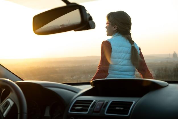 Vista desde el interior de una mujer joven de pie cerca de su coche disfrutando de la cálida vista del atardecer.