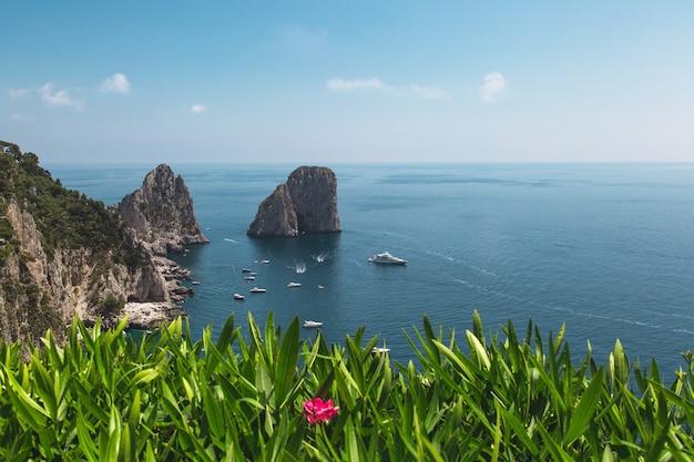 Vista desde los jardines de augusto en la costa de capri y las rocas de faraglioni. italia.
