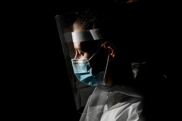 Vista de joven en máscara médica y pantalla protectora que mirando hacia abajo.