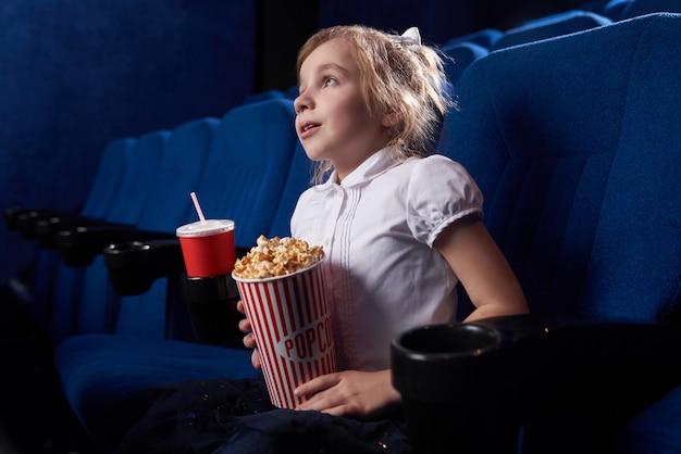 Vista desde el lado de la niña viendo una película emocionada en el cine