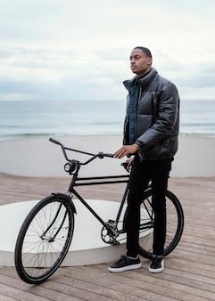 Vista larga del hombre con su bicicleta