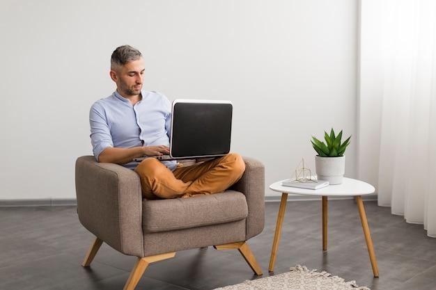Vista larga hombre usando su computadora portátil en interiores