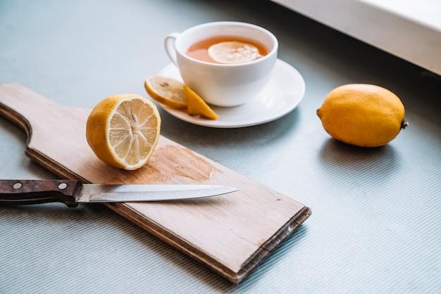 Vista larga taza de café y mitades de limón