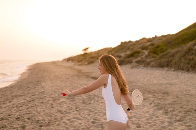 Vista lateral de la adolescente jugando al tenis en la playa de arena